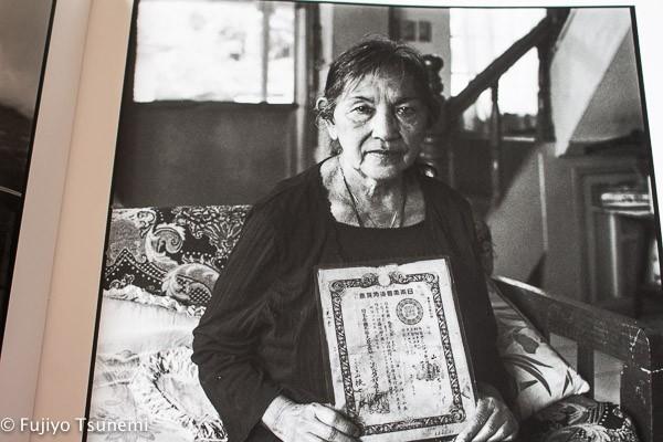 (写真)父の日本旅券を手にする2世の女性。親族の身元を確定できる書類が残っていた幸運で珍しいケースだという。