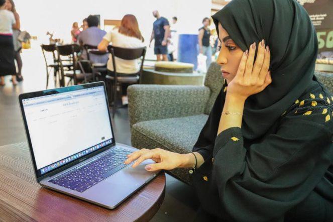 メイクをするイスラム教徒女性パソコンを眺めるアラブ女性